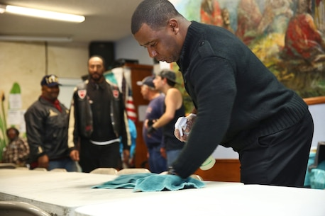 Sergeant Harold Lambert, career planner, Combat Logistics Battalion 1, Combat Logistics Regiment 1, 1st Marine Logistics Group, cleans tables at the Bread of Life Rescue Mission in Oceanside, Calif., Jan. 28, 2014. Nine Marines and one sailor from Camp Pendleton, with the help of several community volunteers, prepared and served a free dinner for local homeless and others in need at the Mission.