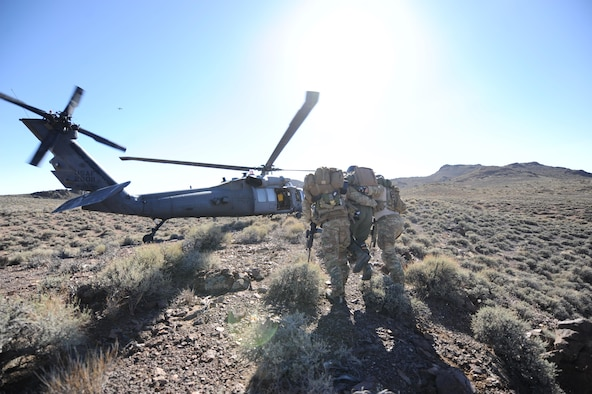 Senior Airman Ronny Epps and Staff Sgt. Matthew Ritchie escort 1st Lt. Kyle Harrington to a waiting HH-60 Pave Hawk during a combat search and rescue scenario for exercise Red Flag 12-4, July 24, 2012, at the Nevada Test and Training Range. After nearly three hours of evading simulated enemy personnel, Harrington successfully made his way 1.8 miles to the extraction zone. Epps and Ritchie are pararescuemen from the 58th Rescue Squadron and Harrington is a B-1 bomber pilot with the 34th Bomb Squadron. (U.S. Air Force photo/Master Sgt. Sonny Cohrs)