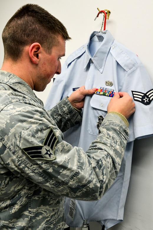 Senior Airman Joshua Cunningham, 460th Mission Support Group Airman category annual award nominee, prepares his uniform before taking an official photograph as part of his annual award package Feb. 3, 2014, at the 460th Space Wing Public Affairs Office on Buckley Air Force Base, Colo. The photograph was one requirement for the annual awards competition, which also included meeting a board of four Buckley chief master sergeants. (U.S. Air Force photo by Senior Airman Riley Johnson/Released)