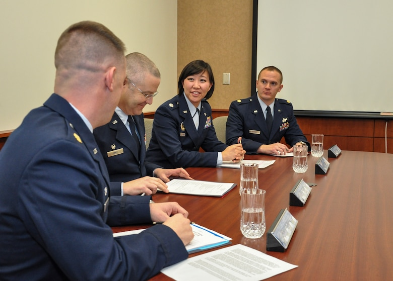 From left, Maj. Nicholas Musgrove, 460th Logistics Readiness Squadron commander; Col. Michael Kindt, 460th Medical Group commander and officer awards board president; Lt. Col. Julie Huygen, 460th Space Wing staff judge advocate; and Maj. Peter Norsky, 460th Operations Group standards and evaluation chief, discuss the annual awards board process Jan. 27, 2014, at the 460th SW headquarters building on Buckley Air Force Base, Colo. All competitors met the annual awards board as part of their overall submission packages. (U.S. Air Force photo by Staff Sgt. Nicholas Rau/Released)