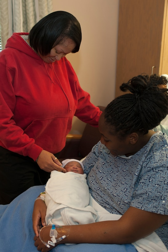 Téa Burke holds her newborn daughter, Noélani Burke, while Teisha Burke, her grandmother, touches her face at the Mike O'Callaghan Federal Medical Center Jan. 30, 2014, at Nellis Air Force Base, Nev. Noélani was delivered shortly after a disgruntled man brandishing a handgun outside the emergency room caused the hospital to be locked down. (U.S. Air Force photo by Airman 1st Class Timothy Young)