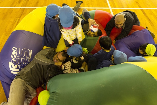 Service members aboard Marine Corps Air Station Iwakuni, Japan, play on an oversize inflatable tube with students from Ekimae Hoikuen Pre-School Jan. 28, 2014, in a community relation visit hosted by the Marine Memorial Chapel. Yasue Miyoshi, teacher with Ekimae Hoikuen Pre-School, said she noticed within the last few years the students open up to military members with their frequent visits to the school. The service members came to the pre-school to teach basic English skills to students and strengthen the Japanese-American relationship.