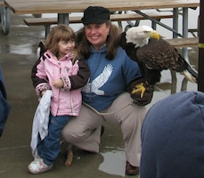 Cathy Spahn, educator from the World Bird Sanctuary in Valley Park, Mo., and Patriot, a rehabilitated bald eagle pose for pictures with visitors at the 4th Annual Kaskaskia Eagle Fest Feb. 1, 2014.