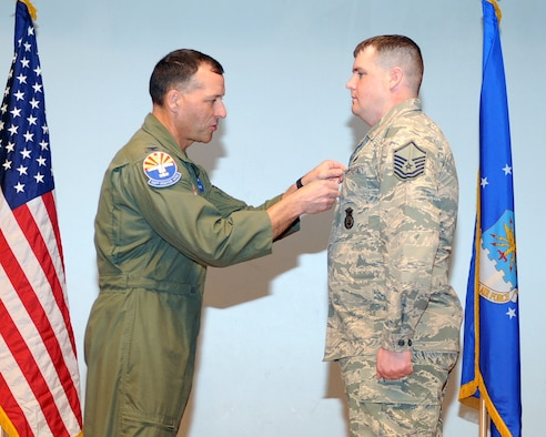U.S. Air Force Col. Kevin Blanchard, 355th Fighter Wing commander, presents Master Sgt. Bruce Archer,  355th Security Forces defender, with a bronze star at Davis-Monthan Air Force Base, Ariz., Jan. 10, 2014. Archer was recognized for the work he did during his year in Afghanistan.(U.S. Air Force photo by A1C Chris Massey/Released)