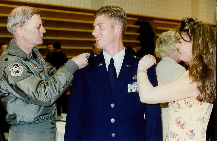Maj. (Dr.) Jeffrey Woolford's wife, Nicole, right, and a mentor, retired Lt. Col. Ron Henry, A-10 thunderbolt II pilot, pin rank on Woolford after he graduated from Uniformed Services University of Health and Sciences School of Medicine. Woolford earned his flight surgeon wings in 2008, and became one of 12 pilot-physicians in the U.S. Air Force.  (U.S. Air Force courtesy photo)
