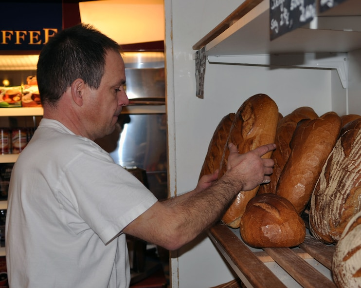 "A local baker ""Meister"" fills up a shelf with fresh bread from the morning baking. There are about 300 different types of bread produced in Germany. The most common and less expensive bread is known as Roggenmischbrot. It is rye mixed bread with wheat or other flour. Bauernbrot is similar to Roggenmischbrot but a bit tastier. It is usually round. Weizenmischbrot is also similar to Roggenmischbrot, it is also light in color, but is made with different proportions of wheat and rye. The shapes of breads are only limited by the bakers' imagination. Bread rolls are very popular in Germany. (U.S. Air Force photo by Iris Reiff/Released)"
