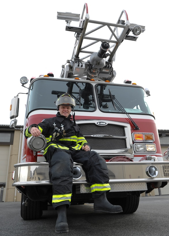 Airman 1st Class Logan Brouse poses with the Quint 1 firefighting truck Jan. 28, 2014, at the fire department on Dover Air Force Base, Del. Brouse is a 436th Civil Engineering Squadron firefighter. (U.S. Air Force photo/Airman 1st Class Zachary Cacicia)