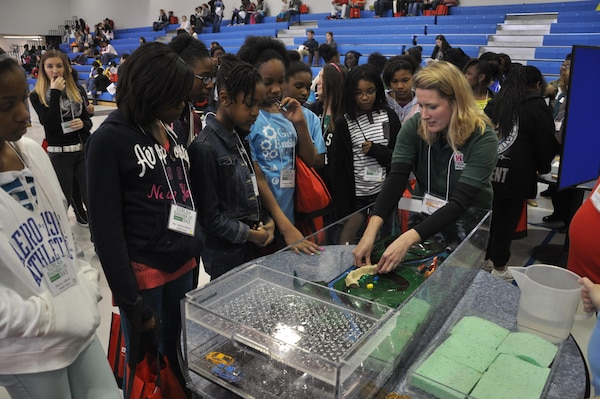 Beth Williams, dam and levee safety program manager for the U.S. Army Corps of Engineers Savannah District, uses a floodplain model to demonstrate the functions of levees at Girls Engineer It Day, Feb. 1. The event reached 350 middle and high-school age females and their parents to promote engineering career fields. USACE photo by Tracy Robillard.