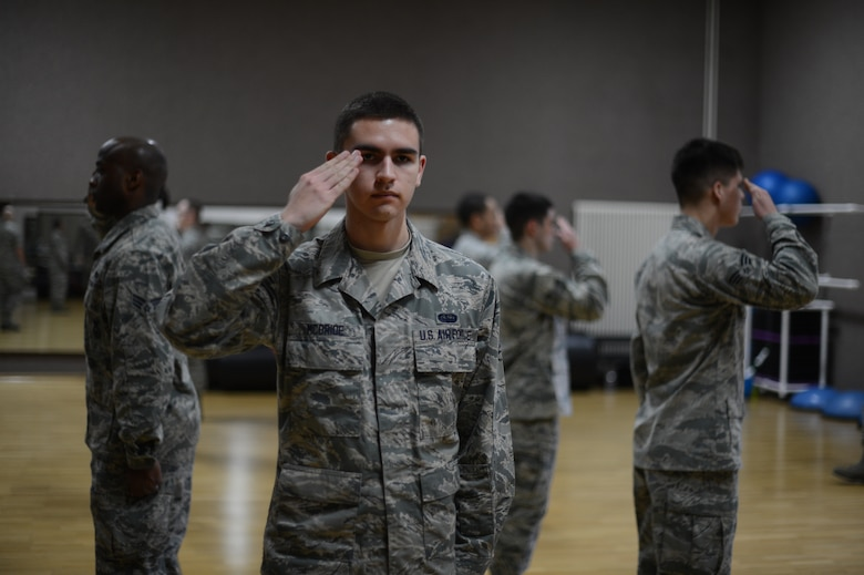U.S. Air Force Airman 1st Class Michael McBride, 606th Air Control Squadron data maintenance technician from Orlando, Fla., practices saluting with his fellow airmen during an honor guard training week at Spangdahlem Air Base, Jan. 27, 2014. The trainees practiced for more than 40 hours to ensure their techniques and military bearing are at the highest level possible. (U.S. Air Force photo by Senior Airman Gustavo Castillo/Released)