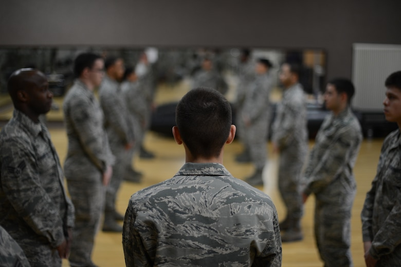 Airmen stand in formation practicing facing movements during an honor guard training week at Spangdahlem Air Base, Jan. 27, 2014. Throughout the week, honor guard trainees spent more than 40 hours practicing drill and ceremony techniques. (U.S. Air Force photo by Senior Airman Gustavo Castillo/Released)