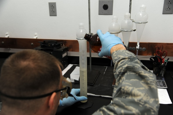 ALTUS AIR FORCE BASE, Okla. – U.S. Air Force Senior Airman Zakkary Wiest and U.S. Air Force Airman 1st Class Damon Kochick, 97th Logistics Readiness Squadron fuels Airmen, run tests in the fuels lab by setting samples and preparing machines Jan. 31, 2014. The fuels department runs several tests on each of the samples taken from fuels systems, tank trucks and storage tanks, which requires much attention to detail. (U.S. Air Force photo by Airman 1st Class J. Zuriel Lee/Released)