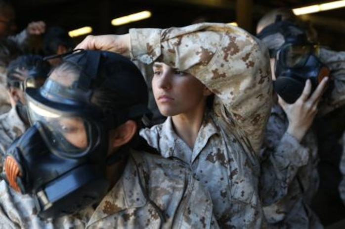 Recruit Alexa Baumert adjusts the straps on Rct. Bianca Saunders' gas mask during chemical and biological warfare defense training Oct. 29, 2013. Baumert, 18, from St. James, N.Y., and Saunders, 23, from Wolcott, Conn., graduated with Platoon 4042, Papa Company, 4th Recruit Training Battalion, on Dec. 20, 2013. (U.S. Marine Corps photo by Cpl. Caitlin Brink).