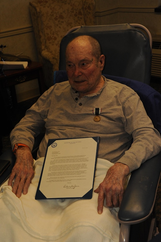 Former Army Air Force Staff Sgt. Kenneth E. Youst, age 92, from Pottsville Pa., and one of 11 surviving Airmen interned at Camp Wauwilermoos, poses with POW medal and letter from the Secretary of the Air Force, Deborah Lee James, at the POW medal presentation Jan. 27, 2014, at the Schuylkill Center Nursing Home, Pottsville, Pa. The POW medal was presented to Youst seven decades later after his internment in a Swiss prison during World War II. (U.S. Air Force photo by Pascual Flores)