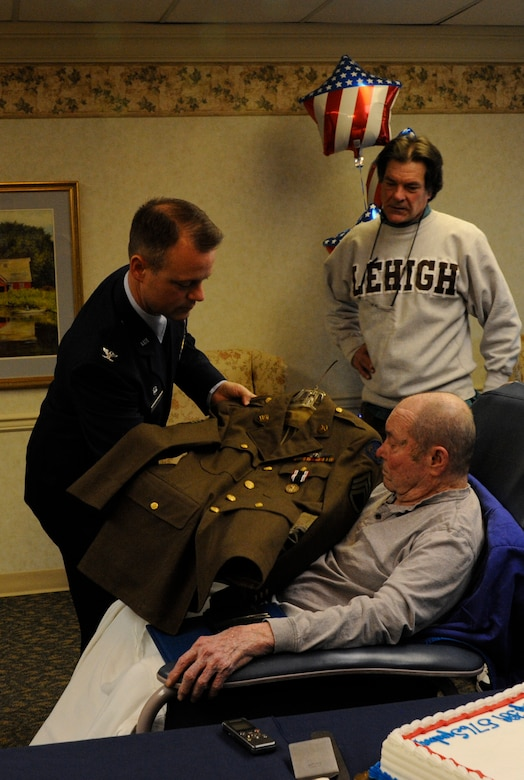 Air Force Col. James C. Hodges, Joint Base McGuire-Dix-Lakehurst and 87th Air Base Wing commander, displays former Army Air Force Staff Sgt. Kenneth E. Yousts' (center) uniform during a Prisoner of War Medal presentation Jan. 27, 2014, at the Schuylkill Center Nursing Home, Pottsville, Pa. The POW medal was presented to Youst seven decades later after his internment in a Swiss prison during World War II. (U.S. Air Force photo by Pascual Flores)