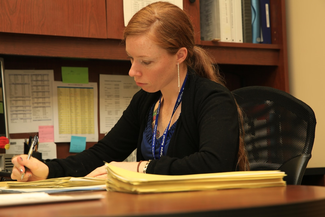 Audrey Mickelson, client service assistant, Navy Marine Corps Relief Society, looks over receipts for quick assist loans to make sure all the information is accurate Feb. 3 at the Village Center Office. The NMCRS offers counseling for young Marines on finances and money management.