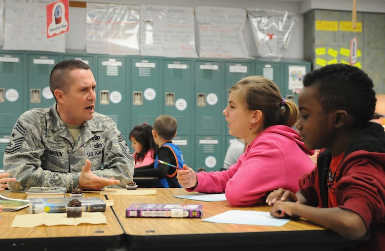 """Chief Master Sgt. Ray Dawson, command chief of the Kentucky Air National Guard's 123rd Airlift Wing in Louisville, Ky., talks with fourth-grade students at Clear Creek Elementary School in Shelbyville, Ky., Jan. 9, 2014, during a visit to thank them for their support of the wing's deployed Airmen. The students """"adopted"""" unit members who are currently serving in Afghanistan, sending them letters and snacks. (U.S. Air National Guard photo by Staff Sgt. Vicky Spesard)"""
