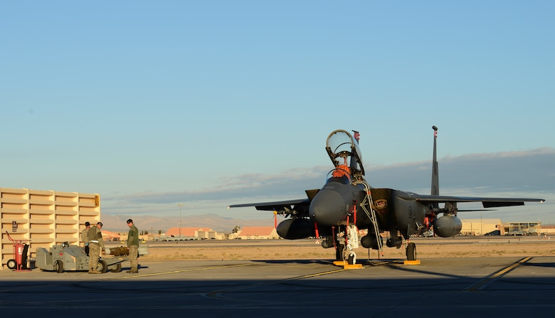 A weapons load crew team prepares to load a GBU-12 munition onto an F-15E Strike Eagle Feb. 4, 2014, at Nellis Air Force Base, Nev. The crew from Mountain Home Air Force Base, Idaho, loaded the rounds in preparation for live-drop training while participating in the combat exercise Red Flag 14-1. By providing realistic combat training in a contested, degraded and operationally limited environment, Red Flag 14-1 provides pilots with real-time war scenarios and helps ground crews test their readiness capabilities. (U.S. Air Force photo by Senior Airman Benjamin Sutton/Released)