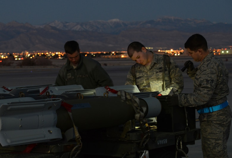 From left, Staff Sgt. Eric Jacewicz, 366th Aircraft Maintenance Squadron weapons load crew team chief,; Airman 1st Class Max Hymes, 366th AMXS weapons load crew two man, and Senior Airman Robert Mills, 366th AMXS load crew three man, all from Mountain Home Air Force Base, Idaho, inventory munitions Feb. 4, 2014, at Nellis Air Force Base, Nev. The Airmen are all on temporary duty assignment to Nellis AFB, participating in Red Flag 14-1. Weapons Airmen loaded live munitions onto F-15E Strike Eagles in order to maximize the training opportunities provided by Red Flag for both air and ground crews. (U.S. Air Force photo by Senior Airman Benjamin Sutton/Released)