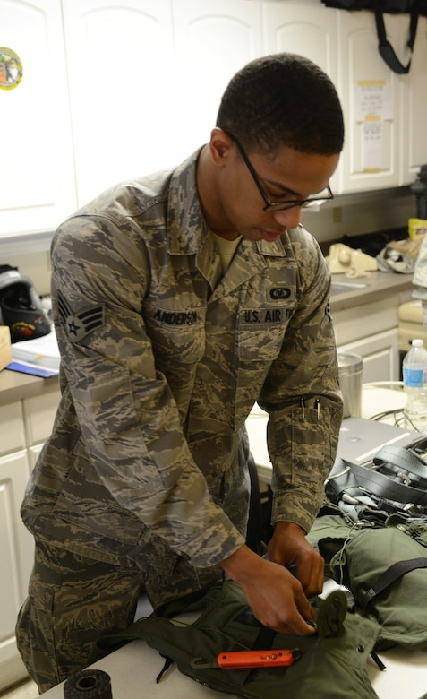 Senior Airman Albert Anderson, 366th Operation Support Squadron aircrew flight equipment technician, from Mountain Home Air Force Base, Idaho, inspects the flight equipment of an F-15E Strike Eagle aircrew member before a sortie Feb. 3, 2014, at Nellis Air Force Base, Nev. Anderson is among more than 3,200 service members participating in the Red Flag 14-1. Red Flag is the U.S. Air Force's premier exercise and gives air and ground crews the opportunity to experience realistic, stressful combat situations in a controlled environment to increase their ability to complete missions and return home. (U.S. Air Force photo by Senior Airman Benjamin Sutton/Released)