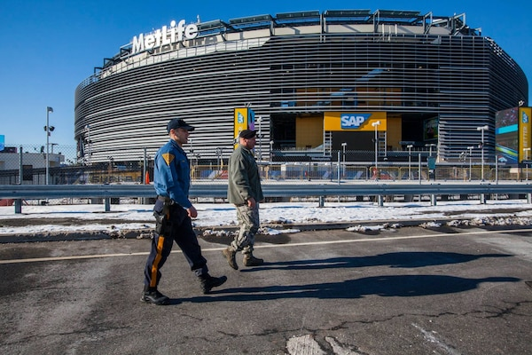 Staff Sgt. Jonathan Arochas, of the New Jersey National Guard's 108th Wing, monitors the perimeter of MetLife Stadium along with a New Jersey state trooper ahead of Super Bowl XLVIII. Guardsmen from six states are on duty supporting the event.