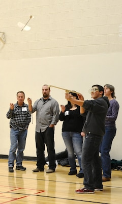 "ALBUQUERQUE, N.M., -- (l-r) Jeff Firebaugh, Chris Parrish, and Ariane Pinson (right) time a student's glider during the ""Elastic-Launched Glider"" event at the Central New Mexico Regional Science Olympiad, Feb. 1."