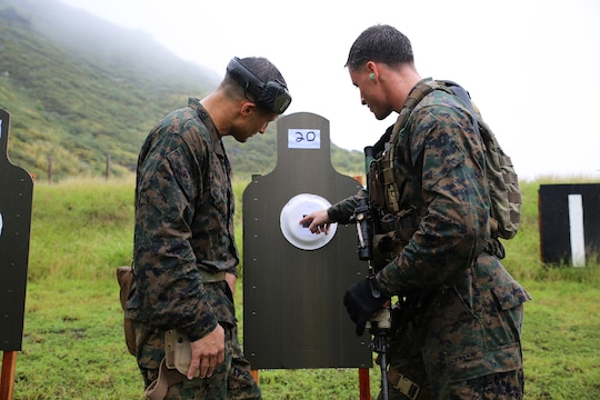 Gunnery Sgt. Jeremiah Dare (left), the Bravo Company operations chief for 3rd Reconnaissance Battalion, coaches Sgt. David Tanney, the jump team leader with Bravo Co., 3rd Recon Bn., during marksmanship training at Kaneohe Bay Range Training Facility, Feb. 4, 2014. (U.S. Marine Corps photo by Lance Cpl. Suzanna Knotts)