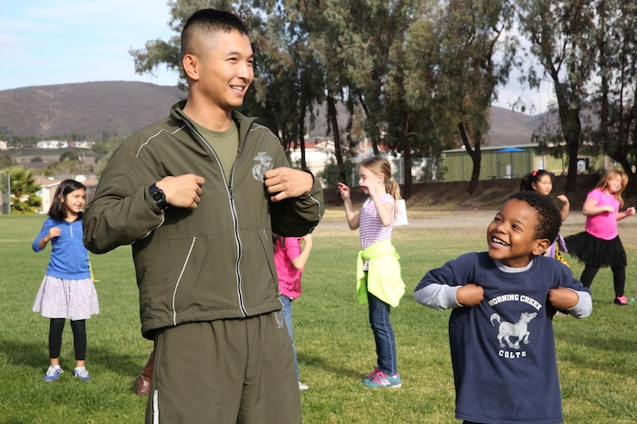 """A Marine volunteer with Marine Aviation Logistics Squadron (MALS) 16, 3rd Marine Aircraft Wing, does the """"Chicken Dance"""" with a Morning Creek Elementary School student during an annual Jog-a-Thon at Morning Creek Elementary School, San Diego, Feb. 6. More than 20 Marines led approximately 800 preschool through fifth-graders in stretching exercises and the """"Chicken Dance"""" before running laps around the playground."""