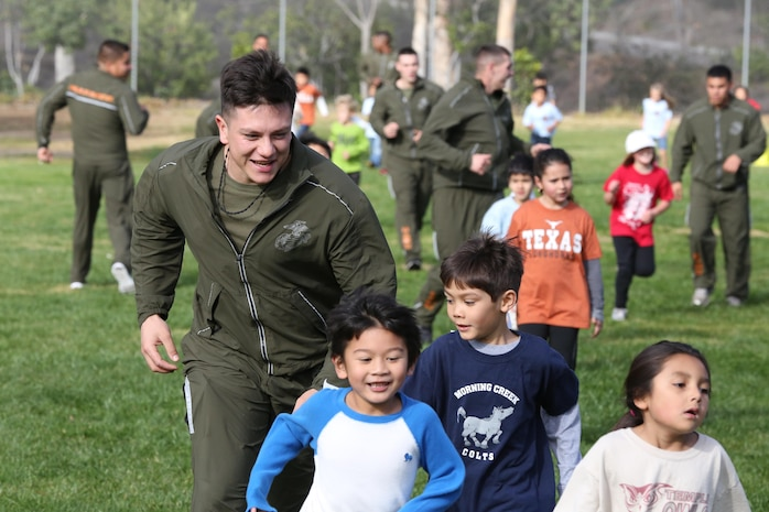 """A Marine volunteer with Marine Aviation Logistics Squadron (MALS) 16, 3rd Marine Aircraft Wing, encourages children of Morning Creek Elementary School, San Diego, during the school's annual Jog-a-Thon Feb. 6. MALS-16 has been involved with the """"Partnerships in Education"""" program with the school for the past eight years."""