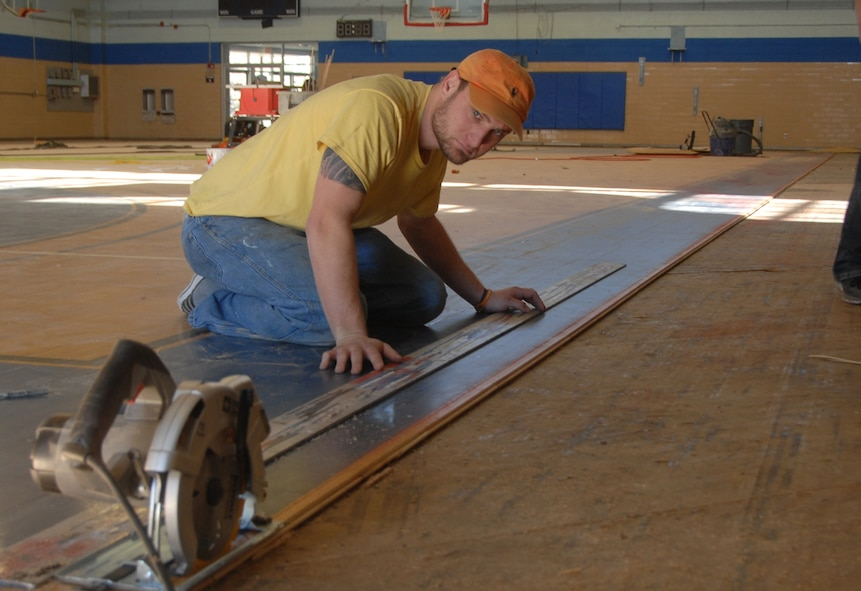 Cory Hughes, an Alabama contractor, measures the perimeter of the existing wood floor at the old basketball court. After edging the floor, a rubber running track will be laid around it. The company's employees will sand and paint the wood floor once the running track is put in place. (U.S. Air Force photo by Misuzu Allen)