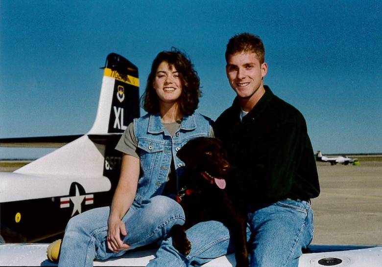 Maj. (Dr.) Jeffrey Woolford and his wife Nicole pose for a photo with their dog on top of a test pilot aircraft. Woolford began his career in the Air Force as an enlisted crew chief. He is now one of 12 pilot-physicians and is currently attending Johns Hopkins University to earn his Master's Degree in Public Health. (U.S. Air Force courtesy photo)