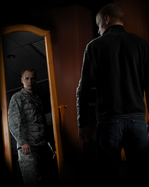 Senior Airman Chase Hedrick, 39th Air Base Wing Public Affairs photojournalist, observes his reflection Feb. 3, 2013, at Incirlik Air Base Turkey. Airmen are Airmen whether in uniform or not, and should ensure their conduct always meets and exceeds the standards of the Air Force they represent. (U.S. Air Force photo illustration by Airman 1st Class Nicole Sikorski/Released)