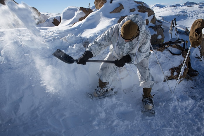 A Marine from Golf Company, 2nd Battalion, 2nd Marine Regiment, 2nd Marine Division digs in the location of his shelter at the top of a mountain during the final six-day field exercise for Mountain Exercise winter training package at MCMWTC Bridgeport, Calif., Feb. 2, 2014. The Warlords and its attached units underwent the winter training package at MCMWTC to prepare for the upcoming a multi-lateral joint and combined exercise Cold Response, which will take place in March of 2014 in Norway.