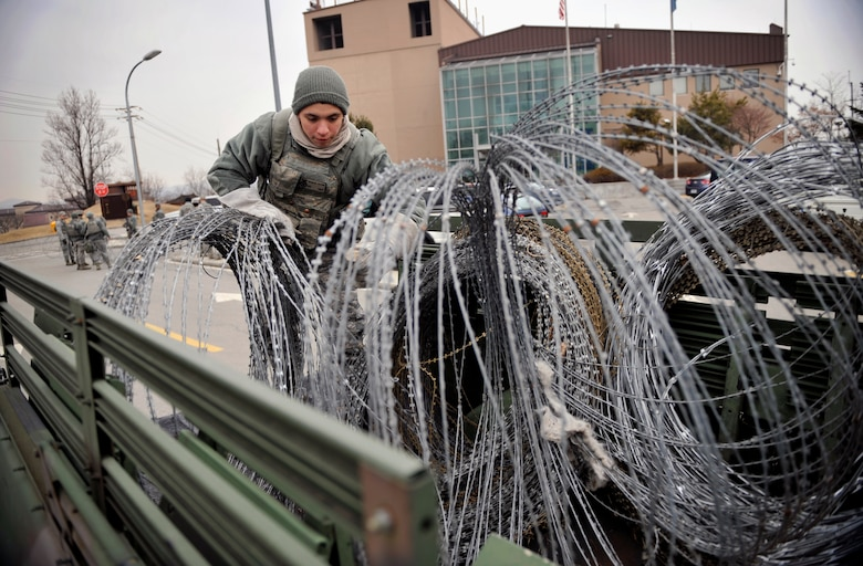 Airman First Class Kevin Garcia, 51st Security Forces Squadron, untangles concertina wire during Operational Readiness Exercise Beverly Midnight 14-02 at Osan Air Base, Republic of Korea, Feb. 9, 2014. Exercises like BM 14-02 test Airmen on their ability to operate and accomplish the mission during war-time contingency operations. (U.S. Air Force photo/Senior Airman Siuta B. Ika)