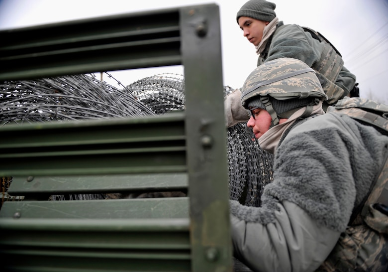 Members of the 51st Security Forces Squadron prepare to unload concertina wire from the bed of a truck to use as a barrier during Operational Readiness Exercise Beverly Midnight 14-02 at Osan Air Base, Republic of Korea, Feb. 9, 2014. During exercises and war-time contingency operations, c-wire is placed strategically around the base. (U.S. Air Force photo/Senior Airman Siuta B. Ika)