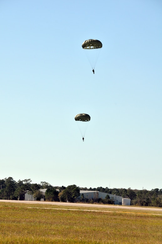 Members from the 147th Reconnaissance Wing Air Support Operations Squadron drift toward the ground after jumping from a HH-60 Pave Hawk at Avon Park Air Force Range, Florida December 16, 2013. Performing exercises at the Florida range allows the airmen to hone the necessary skill sets to perform their jobs and missions in an environment that allows for the use of live fighter aircraft and live munitions to replicate real-life warfighting scenarios. National Guard photo by 2nd Lt. Alicia Lacy.