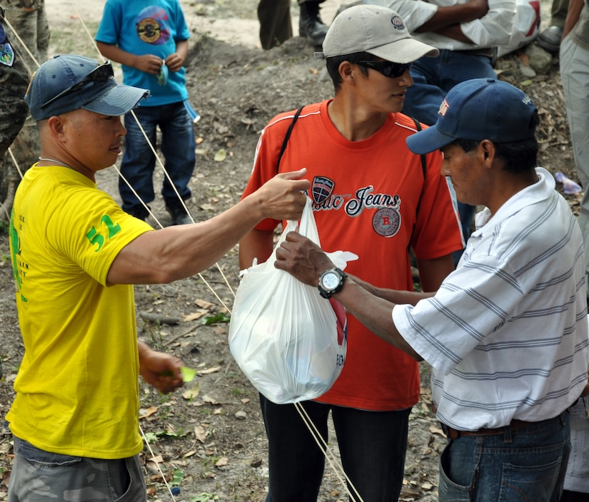 """U.S. Army Sgt. Maj. Thinh Huynh, Army Forces Battalion, delivers a bag of food to a Honduran family during the 52nd Joint Task Force-Bravo """"Chapel Hike"""" in Honduras, Feb. 8, 2014.  More than 120 members of Joint Task Force-Bravo spent the day delivering more than 2,400 pounds of food and medical supplies to families in need in the mountain village of La Laguna, Honduras.  To deliver the supplies, Task Force members carried the items on a more than seven-mile round trip hike, with an elevation gain of 1,700 feet.  All of the food and supplies were purchased with funds donated by Task Force members.  (U.S. Air Force photo by Capt. Zach Anderson)"""