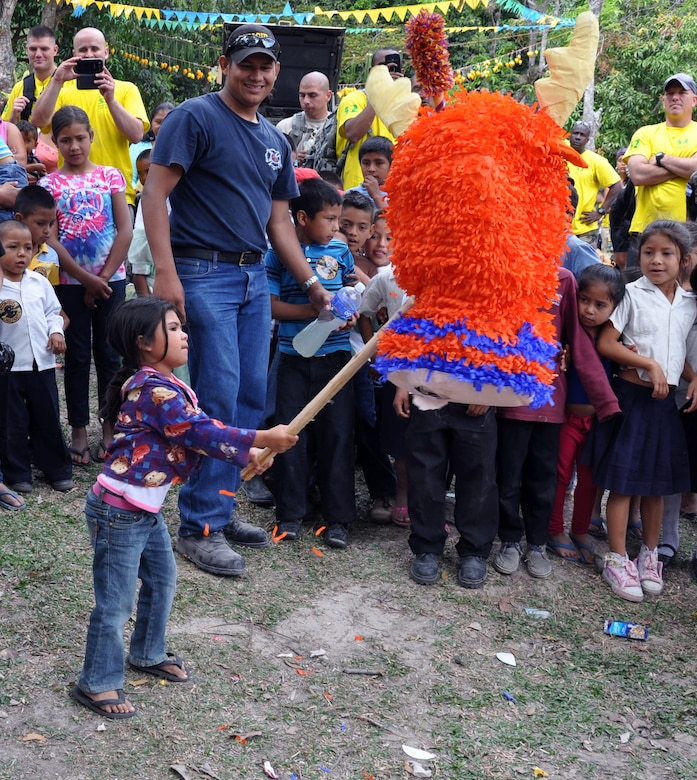 """A young Honduran girl takes a swing at a pinata during the 52nd Joint Task Force-Bravo """"Chapel Hike"""" in Honduras, Feb. 8, 2014.  More than 120 members of Joint Task Force-Bravo spent the day delivering more than 2,400 pounds of food and medical supplies to families in need in the mountain village of La Laguna, Honduras.  To deliver the supplies, Task Force members carried the items on a more than seven-mile round trip hike, with an elevation gain of 1,700 feet.  All of the food and supplies were purchased with funds donated by Task Force members.  (U.S. Air Force photo by Capt. Zach Anderson)"""