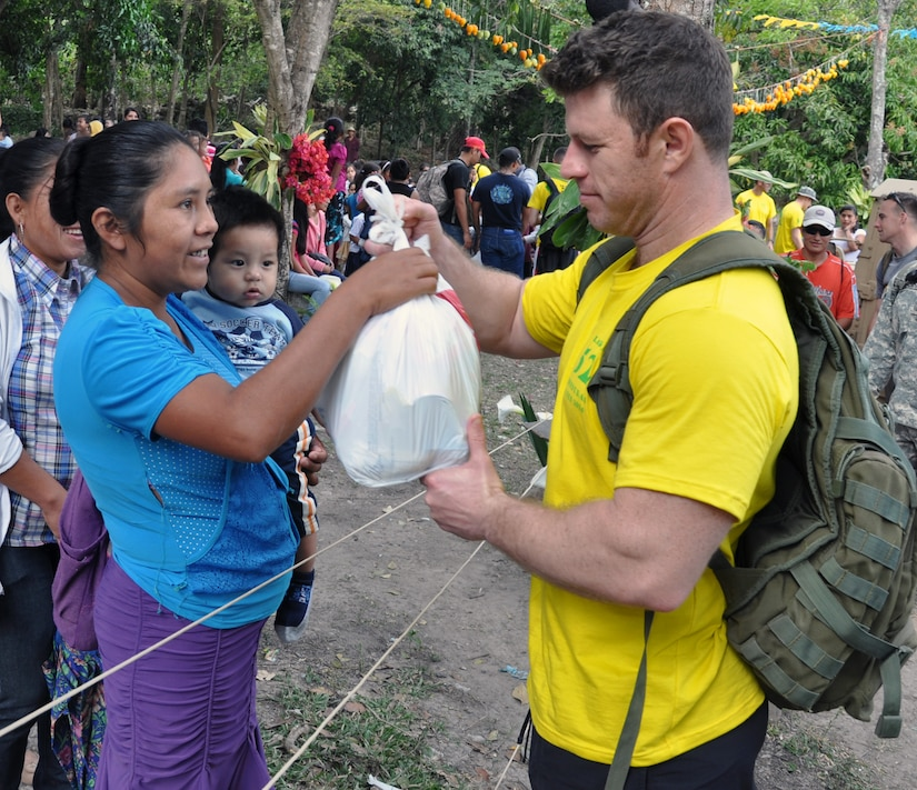 """U.S. Army Maj. Brad Miller delivers a bag food and supplies to a Honduran family during the 52nd Joint Task Force-Bravo """"Chapel Hike"""" in Honduras, Feb. 8, 2014.  More than 120 members of Joint Task Force-Bravo spent the day delivering more than 2,400 pounds of food and medical supplies to families in need in the mountain village of La Laguna, Honduras.  To deliver the supplies, Task Force members carried the items on a more than seven-mile round trip hike, with an elevation gain of 1,700 feet.  All of the food and supplies were purchased with funds donated by Task Force members.  (U.S. Air Force photo by Capt. Zach Anderson)"""
