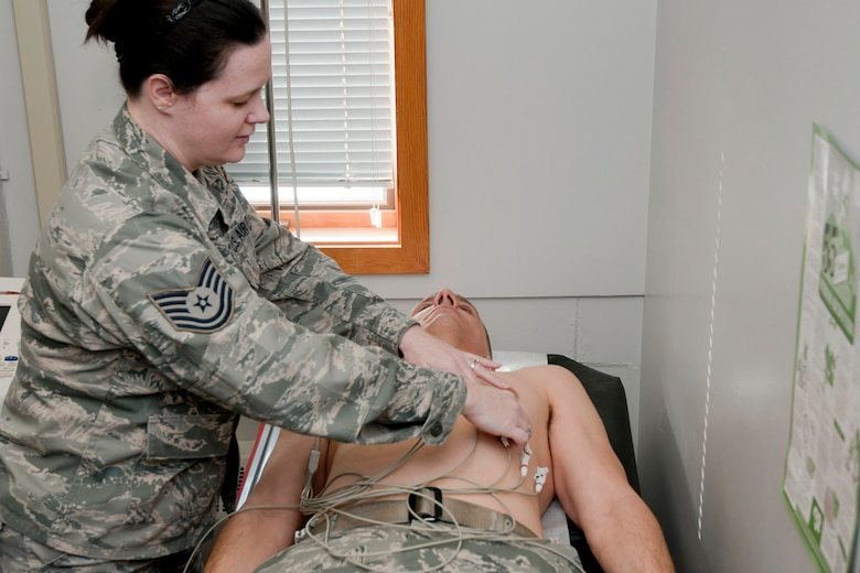 Tech. Sgt. Stephanie Ploeger (left) hooks Master Sgt. Mike Johnson (right) up to an electrocardiogram (EKG) machine for simulated testing on his heart in the exam room of the 132nd Fighter Wing (132FW) Medical Facility, Des Moines, Iowa on February 7, 2014.  (U.S. Air National Guard photo by Staff Sgt. Linda K. Burger/Released)