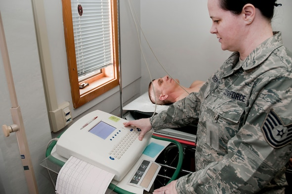 Tech. Sgt. Stephanie Ploeger (front right) hooks Master Sgt. Mike Johnson (back middle) up to an electrocardiogram (EKG) machine for simulated testing on his heart in the exam room of the 132nd Fighter Wing (132FW) Medical Facility, Des Moines, Iowa on February 7, 2014.  (U.S. Air National Guard photo by Staff Sgt. Linda K. Burger/Released)