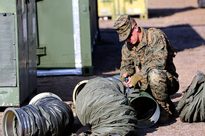 Lance Cpl. Alexander J. Smith, a field radio repairman with 9th Communication Battalion, links tubing together at a combat operations center exercise aboard Camp Pendleton, Calif., Feb. 5. The exercise created a realistic environment for Marines to quickly and effectively establishes a center of operations.