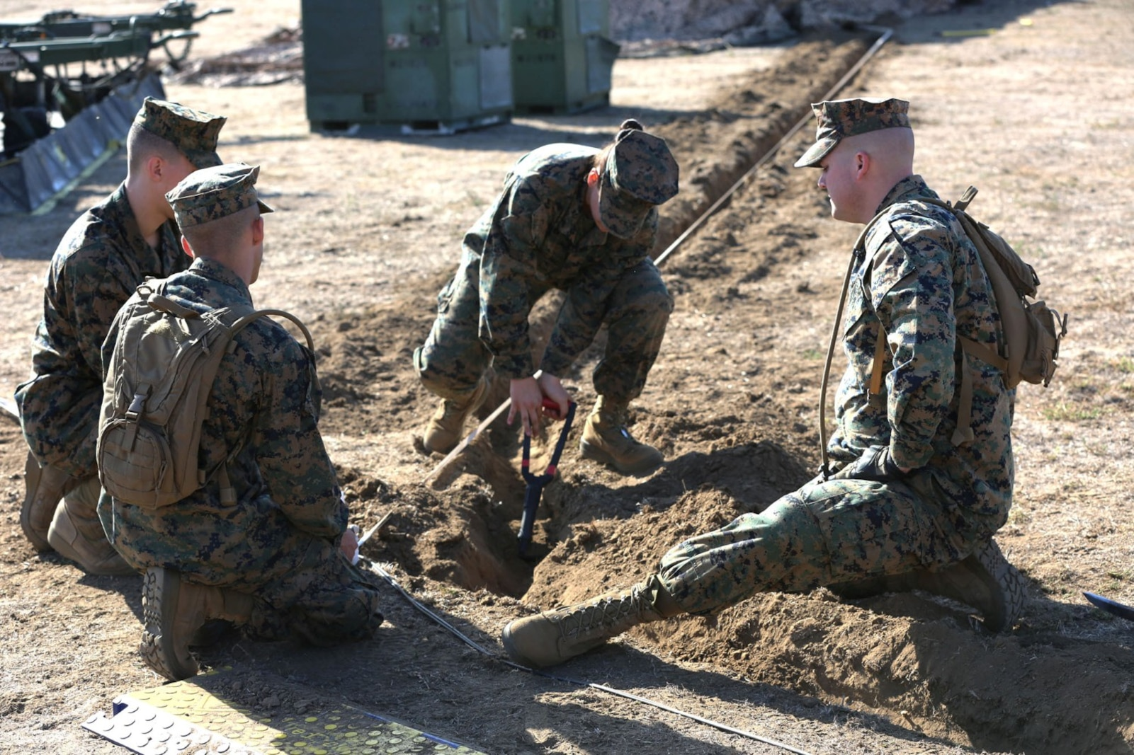 Marines with 1st Marine Expeditionary Brigade dig trenches to lay wires during a combat operations center exercise aboard Camp Pendleton, Calif., Feb. 5. The exercise created a realistic environment for Marines to quickly and effectively establishes a center of operations.