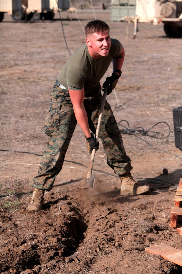 Lance Cpl. Connor Polston, a special intelligence system administrator with 1st Intelligence Battalion, digs a trench to lay wiring at a combat operations center exercise aboard Camp Pendleton, Calif., Feb. 5. The exercise created a realistic environment for Marines to quickly and effectively establishes a center of operations.