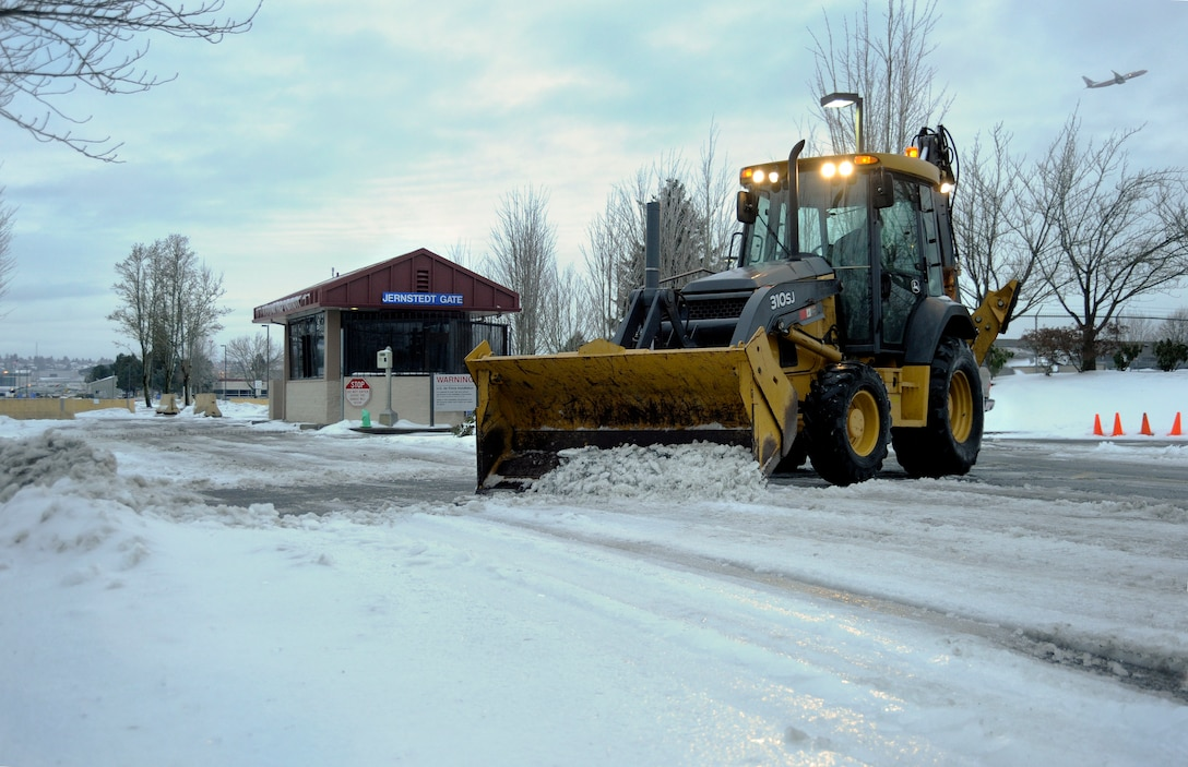 Oregon Air Guard Senior Airmen Andrew Wolf, 142nd Fighter Wing Civil Engineer Squadron, works to remove snow and ice from the main gate at the Portland Air National Guard Base, Ore., Feb. 10, 2014.  The February Unit Training Assembly was cancelled, but a small group from the CES worked over the weekend to keep the base running and the alert mission operational during the winter storm that hit the Pacific Northwest region. (Air National Guard photo by Tech. Sgt. John Hughel, 142nd Fighter Wing Public Affairs/Released)