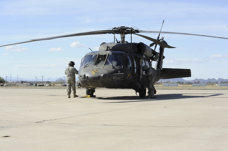 Members of the U.S. Army prepare a UH-60 Black Hawk for refueling after landing at Davis-Monthan Air Force Base, Ariz., Feb. 7, 2014. The aircraft and personnel, assigned to the 3-227th Assault Helicopter Battalion, 1st Air Calvary Brigade, 1st Cavalry Division out of Fort Hood, Texas, refueled at D-M before continuing to California where they will participate in a training exercise. (U.S. Air Force photo by Airman 1st Class Betty R. Chevalier/released)
