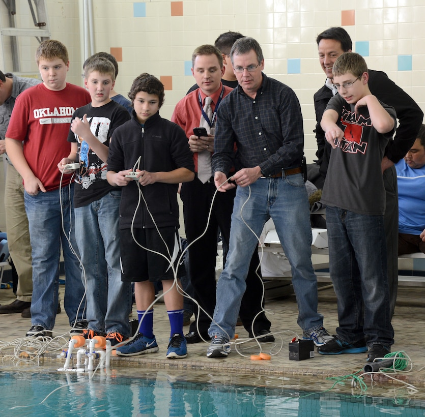 With the help of their Tinker mentors, Carl Albert Middle School students Matt Salsbury, Gregory Aldridge, Roshan Abhayagoonawardhana and Jakob Carlson, from left, work together to maneuver their SeaPerch Remotely Operated Vehicle through obstacles set up in the Midwest City YMCA pool last week. Watching the students are Don Arrowood, B-52 Program Office; Rich Desmond, 555th Software Maintenance Group; and Jeff Catron, Air Force Sustainment Center Engineering Directorate. (Air Force photo by Micah Garbarino)
