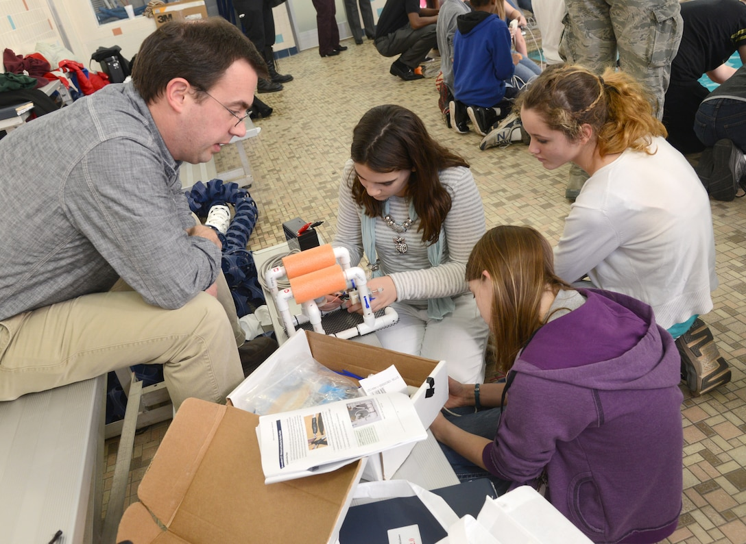 Rhett Butler, with the Air Force Life Cycle Management Center's E3-AWACS Division, helps Sophia Smith, Hayley Allen and Elexis Speers, all eighth graders from Carl Albert Middle School, put the finishing touches on their SeaPerch ROV. (Air Force photo by Kelly White)