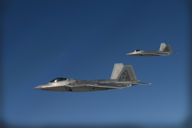 Two F-22 Raptors from the 1st Fighter Wing, Joint Base Langley-Eustis, Va., fly beside a KC-135 Stratotanker from the 93rd Air Refueling Squadron Fairchild Air Force Base, Wash., while waiting for their wingmen to receive fuel over the Nevada Test and Training Range during Red Flag 14-1 at Nellis AFB, Nev., Feb. 6, 2014. Red Flag gives aircrews and air support operations service members from various airframes, military services, and allied countries an opportunity to integrate and practice combat operations. (U.S. Air Force photo by Senior Airman Benjamin Sutton/Released)