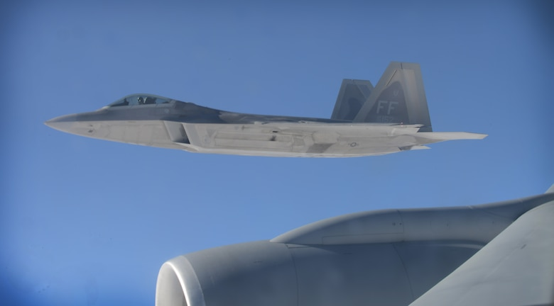 An F-22 Raptor from the 1st Fighter Wing, Joint Base Langley-Eustis, Va., flies beside a KC-135 Stratotanker from the 93rd Air Refueling Squadron Fairchild Air Force Base, Wash., over the Nevada Test and Training Range during Red Flag 14-1 at Nellis AFB, Nev., Feb. 6, 2014. After receiving fuel the aircrews wait for their wingmen before continuing on with their specific mission. The exercise is conducted above the 2.9 million square acre NTTR north of Las Vegas. (U.S. Air Force photo by Senior Airman Benjamin Sutton/Released)