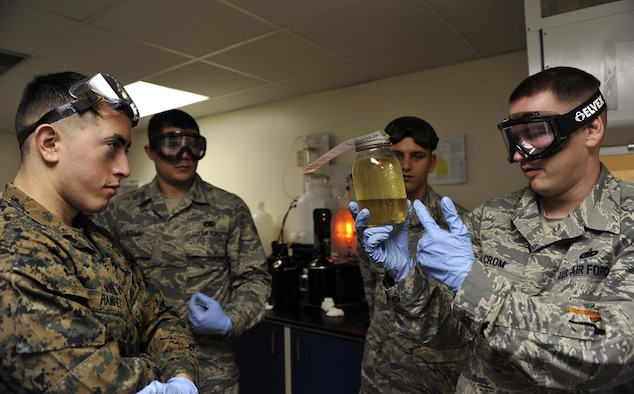 Tech. Sgt. Richard Crom presents a container of a fuel and water mixture during a field exchange program Feb. 6, 2014, at Kadena Air Base, Japan. The Field Exchange Program is the first of its kind which combines the Air Force and Marine Corps training on fuel procedures. Crom is the 18th Logistics Readiness Squadron NCO in charge of the fuel lab. (U.S. Air Force photo/Naoto Anazawa)